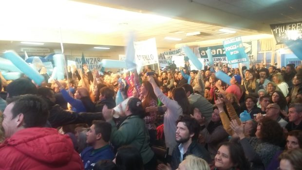En el interior del salón los seguidores de Poggi acompañan con aplausos y cánticos el discurso del dirigente.